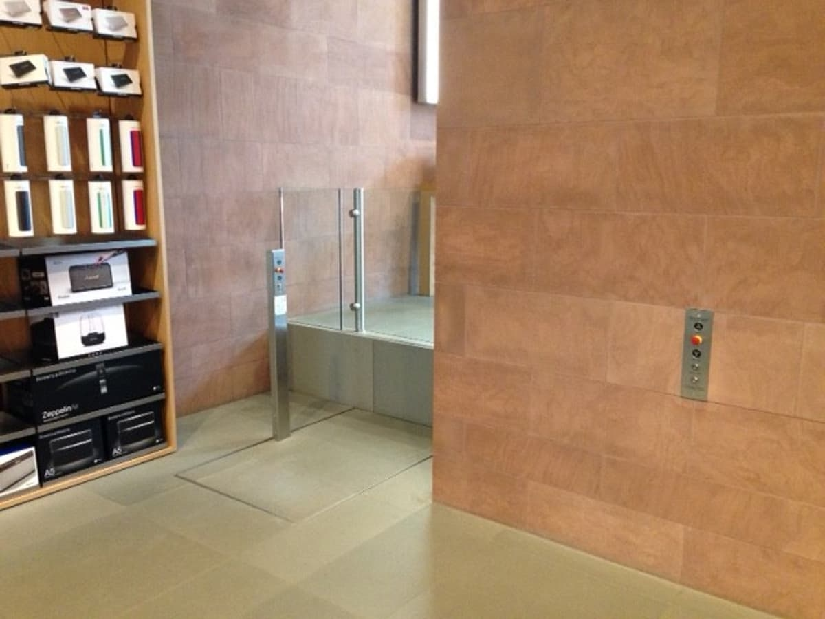 A lift for wheelchair access at rest sitting flush with lower landing level. There is a glass gate at the upper landing level and an on lift button post. This lift is in an Apple store in France.