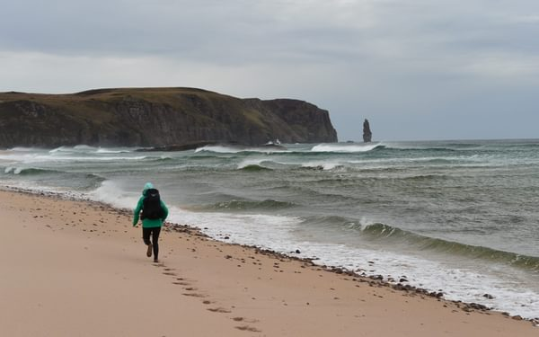 Lily running through Sandwood Bay, Scotland. Photo by Chris Councell.