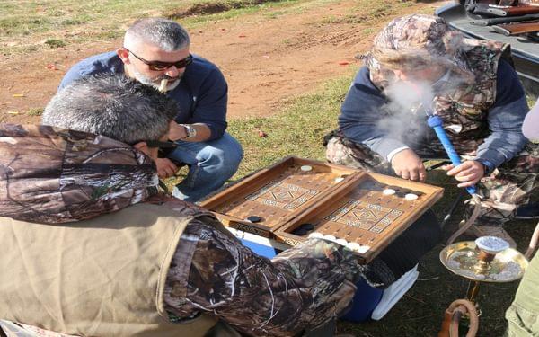 Hunters indulging in backgammon and shisha