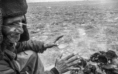 Yak handler Safdar warming his hands