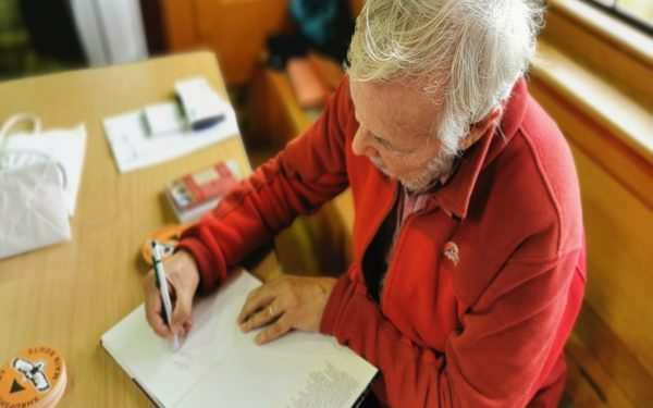 John signing the old books