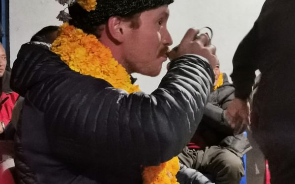 A member of our group sits like a king; covered in marigold garlands and drinking rice wine