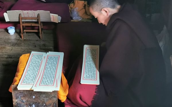 A monk reading prayers at Thubtan Chholing Monastery in Junbesi