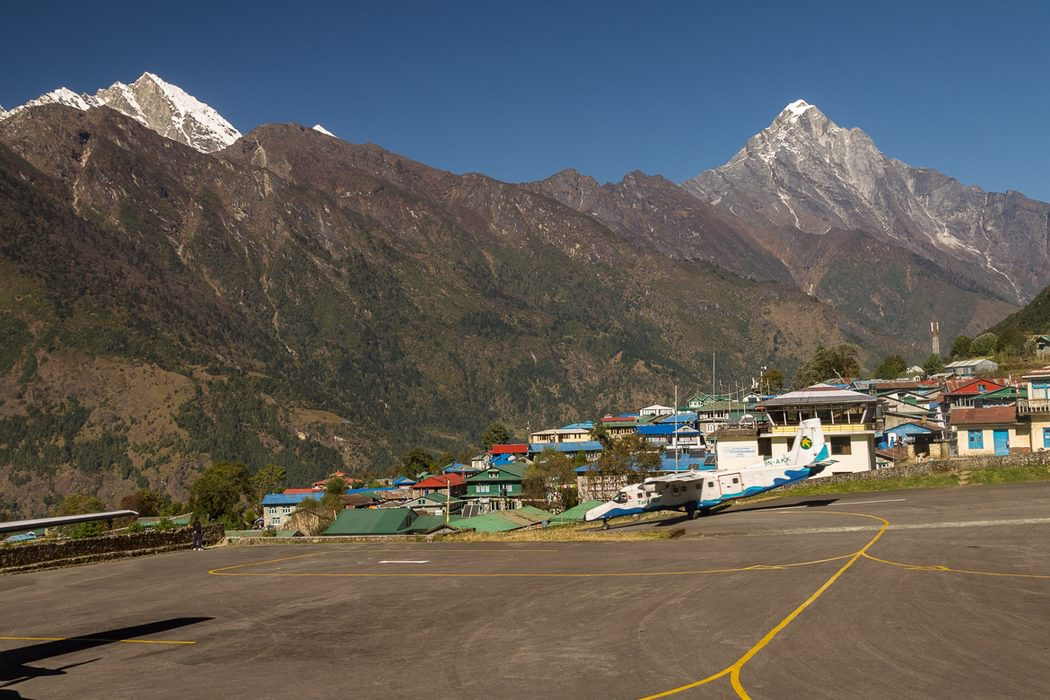 A  Tara  Air  Dornier  Do 228 212 Aircraft Speeds Down The Runway At  Lukla  Airport In The Background Are  Karyolung Left 6511M And  Nupla 5885M