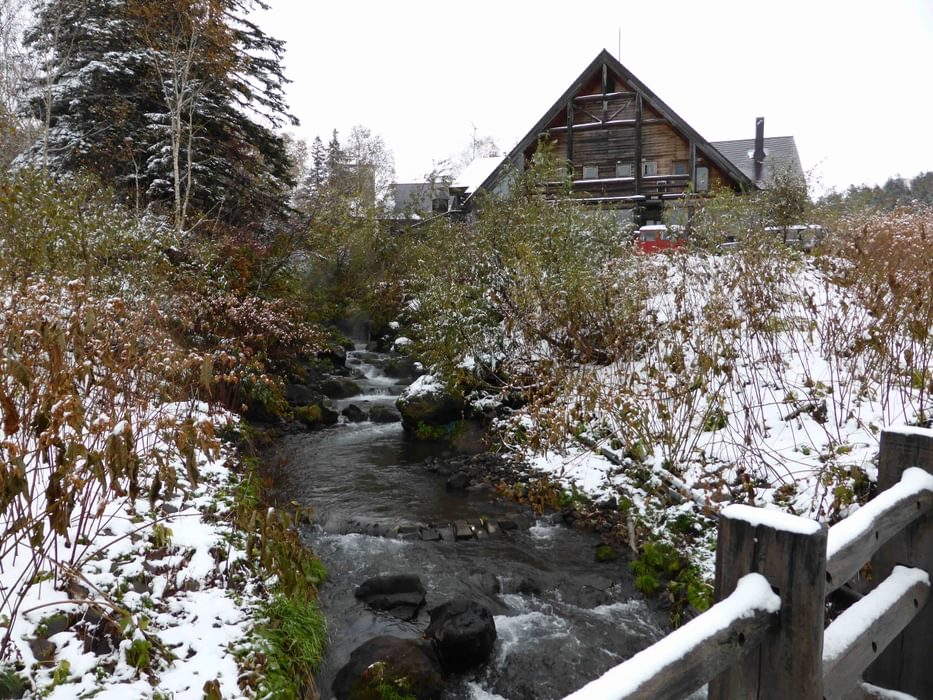 A Mountain Hut Next To A Steaming Thermal River In Daisetsuzan