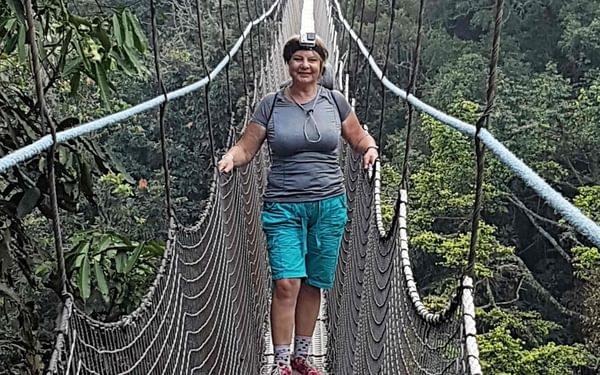 Hiking Across A Suspension Bridge In  Rwanda