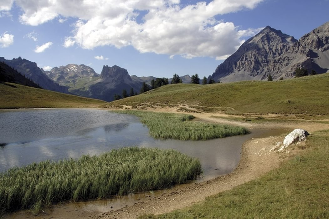 A pleasant little lake sits on the grassy Col des Thures high above the Vallée Étroite. Seen on a variant route of the GR5 trek through France.