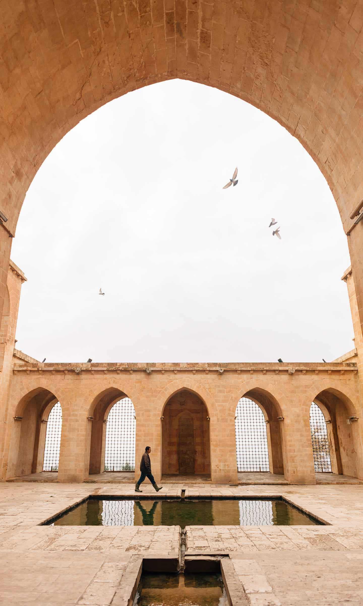 A Man Walks Across a Medrese in Mardin, Turkey