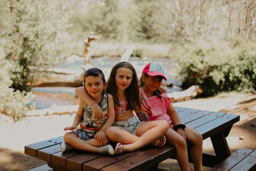 My three kids sitting on a picnic table