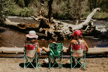 My three kids sitting on camp chairs near a fallen tree and a river
