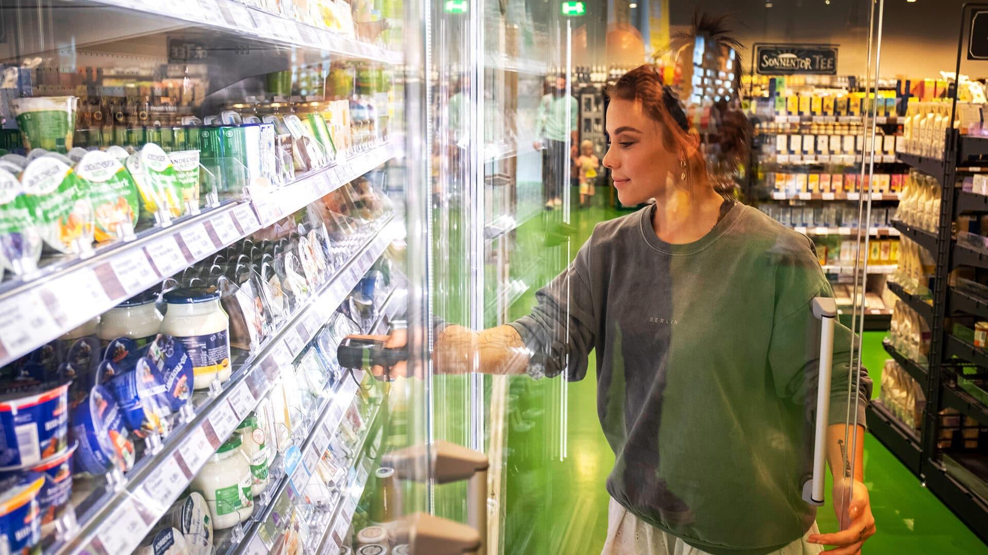 Frau nimmt ein Produkt aus der Kühltruhe