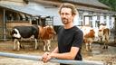 Mann mit Brille steht vor einem Kuhgehege