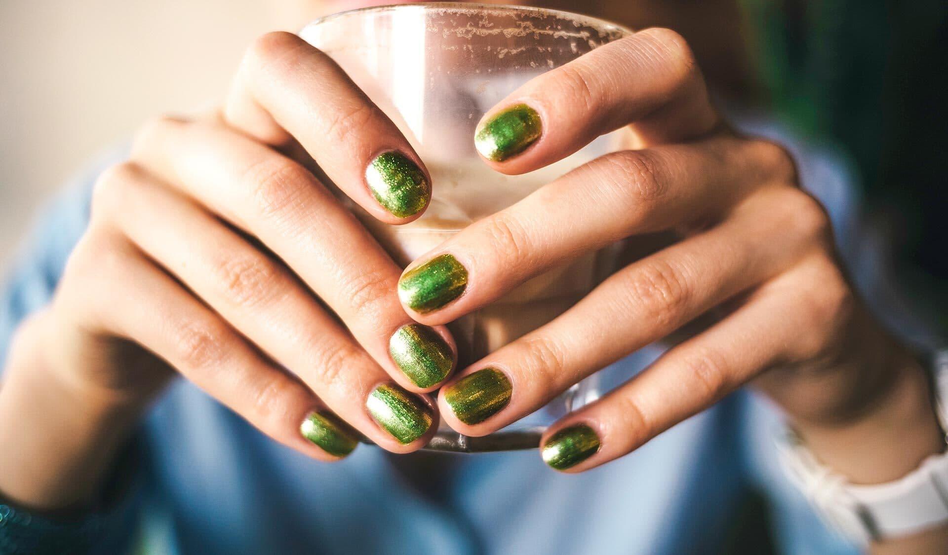 Zwei Frauenhände mit grün lackierten Nägeln halten ein Glas.