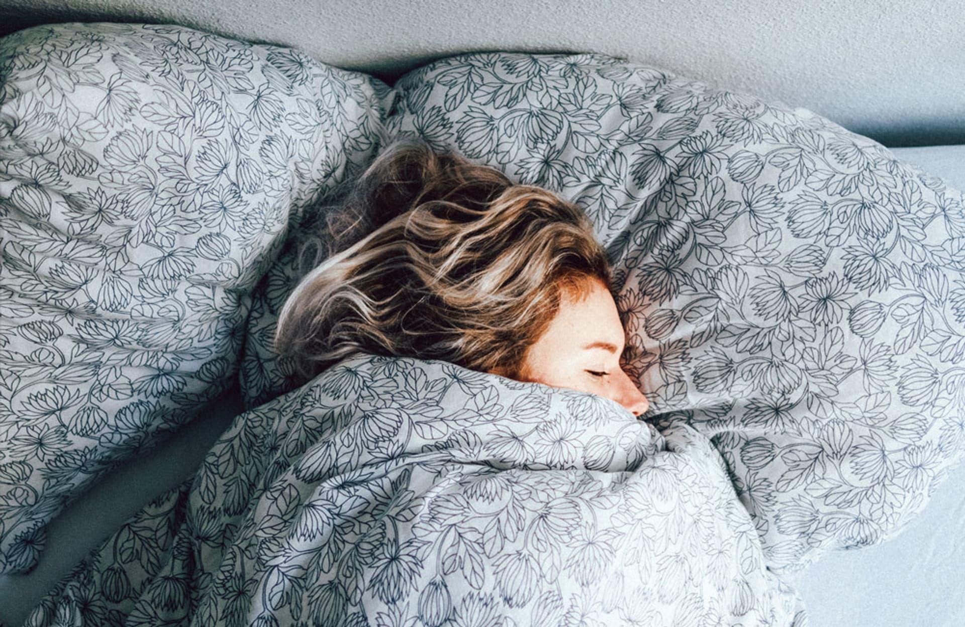 Eine Frau liegt zugedeckt im Bett und schläft.