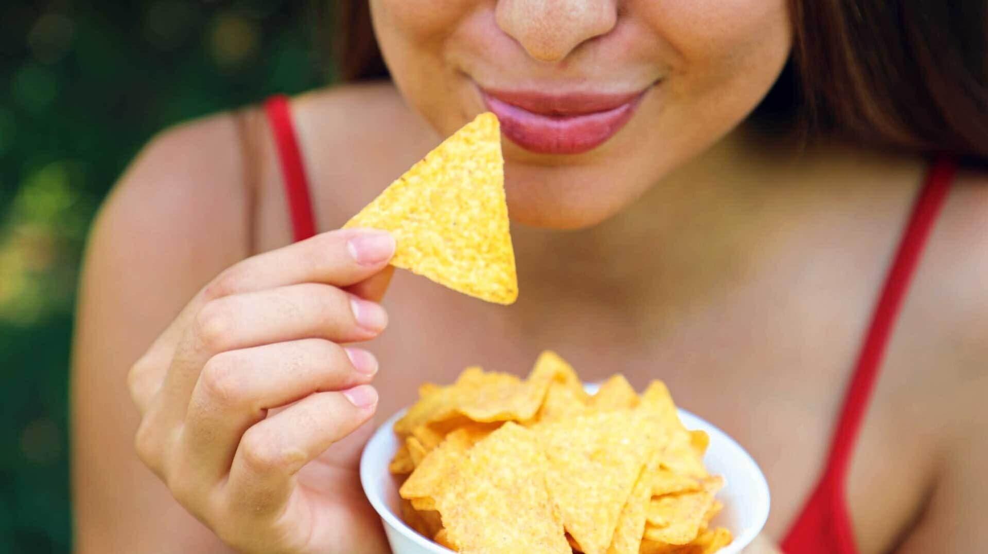 Eine Frau hält einen Tortilla Chip in der Hand und führt ihn zum Mund.