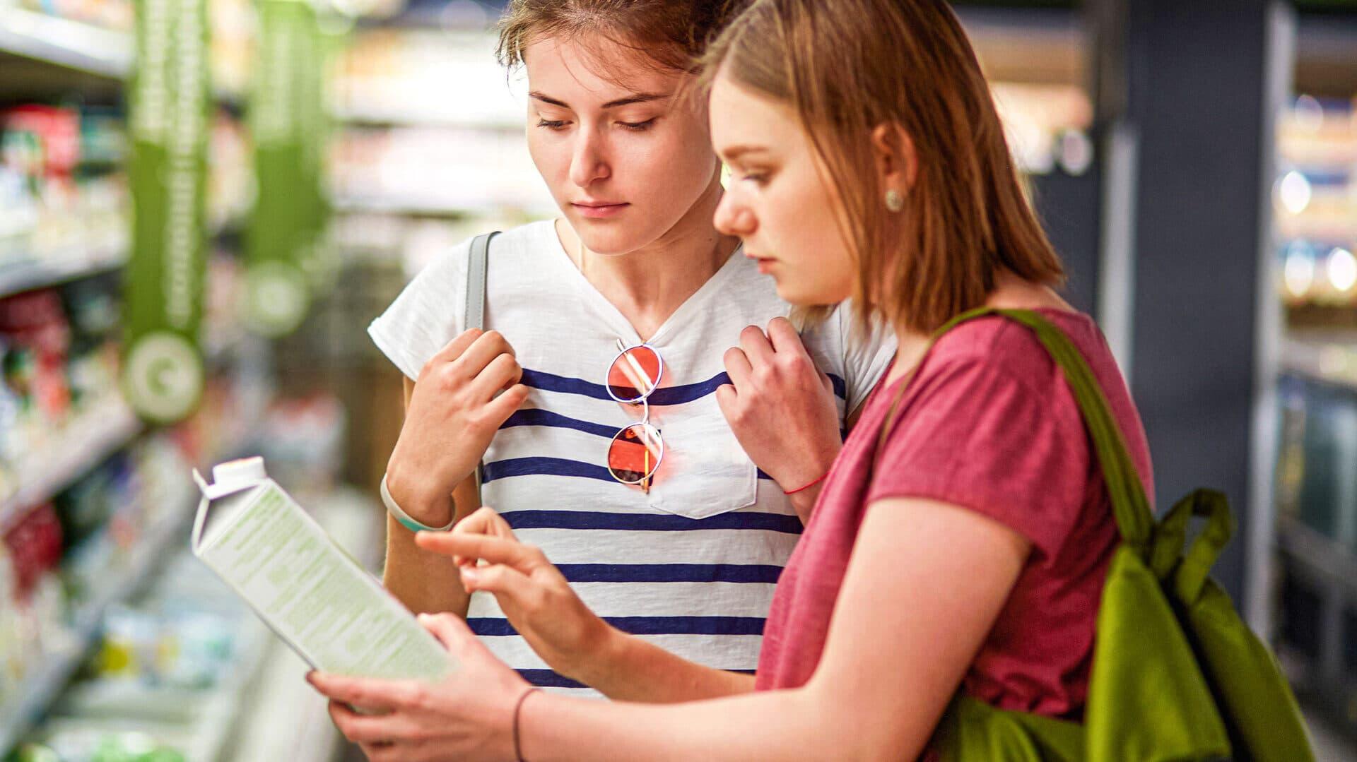 Zwei Frauen lesen die Zutatenliste auf einem Haferdrink
