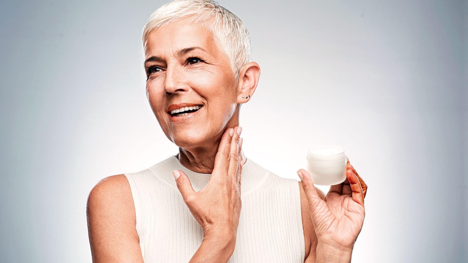 Eine Frau mit kurzen grauen haaren cremt sich den Hals ein