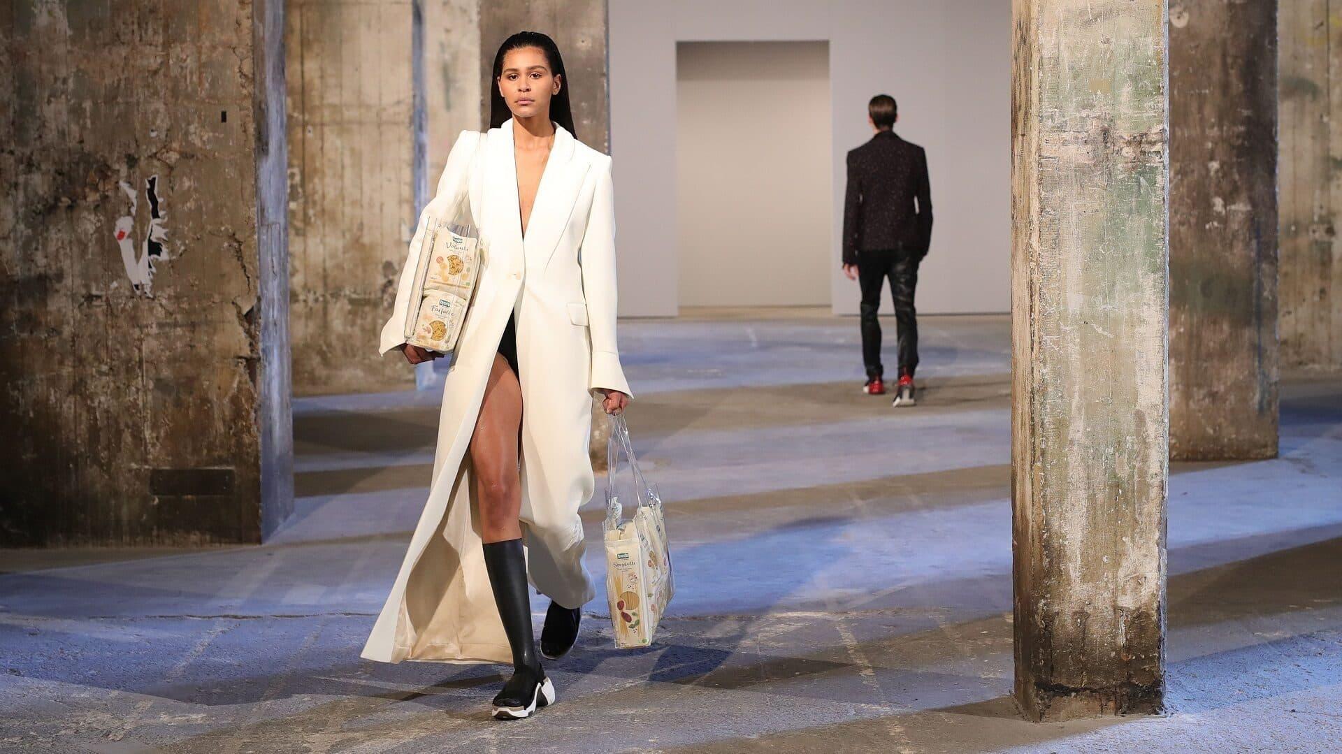 Ein Model in weißem Mantel läuft mit transparenten Taschen gefüllt mit Pasta über den Catwalk.