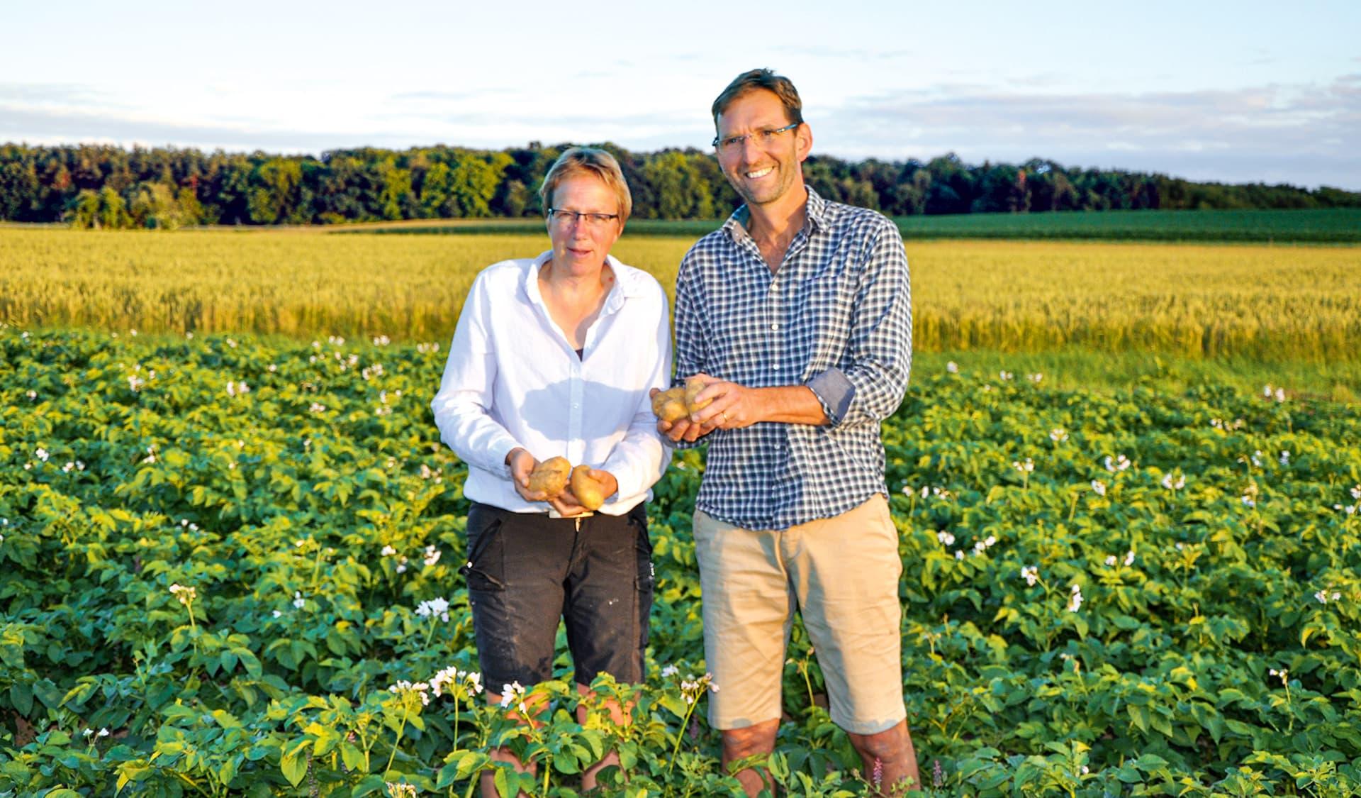 Petra Sandjohann und ihr Mann Bernhard Schreyer in ihrem Kartoffelfeld stehend.