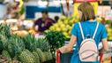 Eine Frau in blauem Kleid mit Einkaufswagen vor einem Tisch mit Ananas.