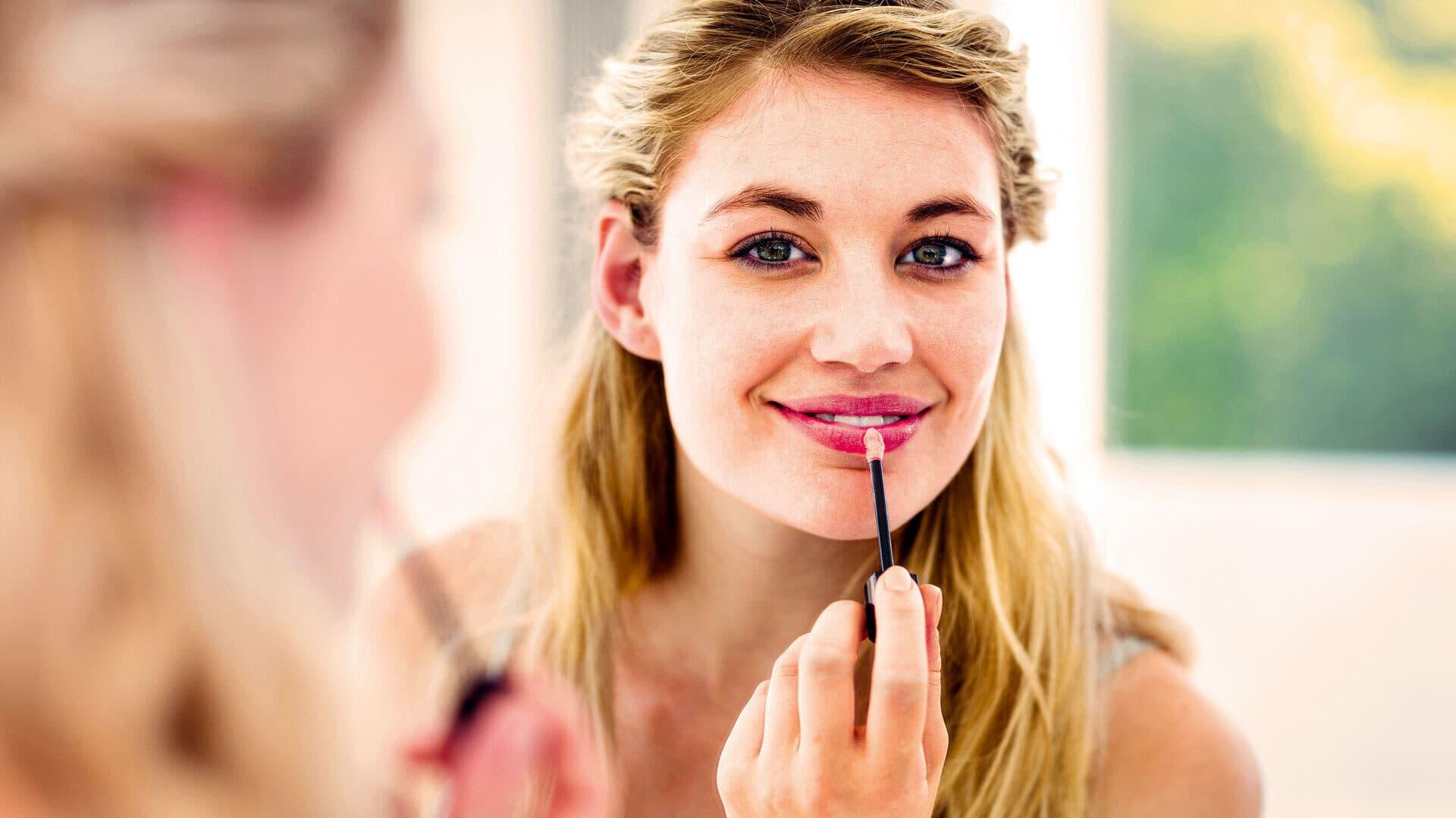Eine Frau trägt Lipgloss auf