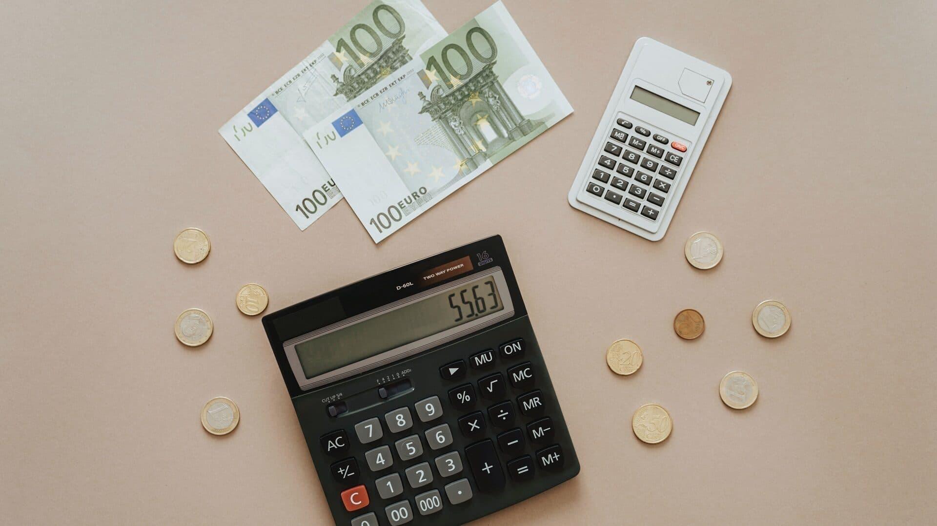 Zwei Taschenrechner, Geldscheine und Münzen