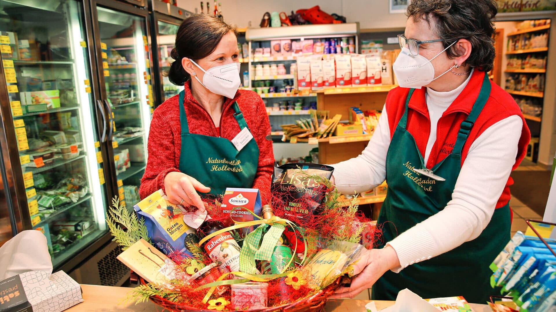Monika und eine Mitarbeiterin beim Packen eines Geschenkkorbes