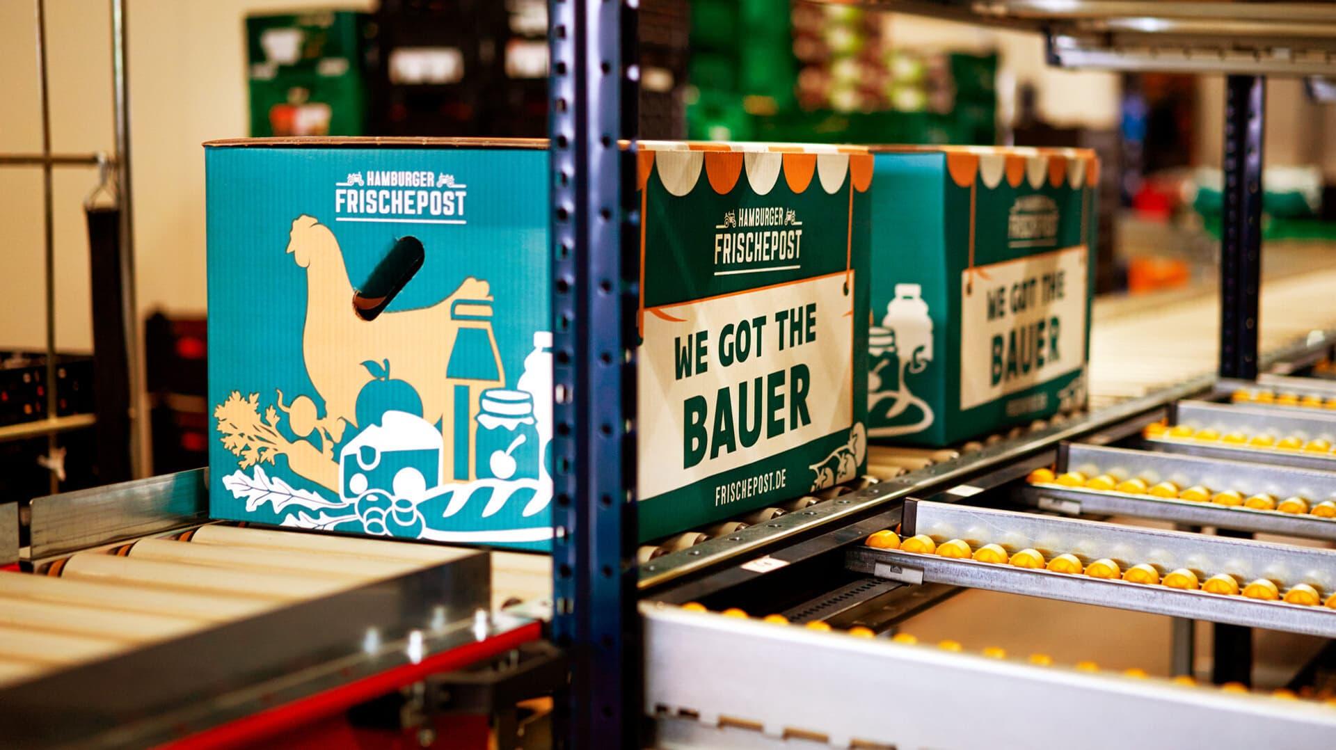 Kisten der Hamburger Frischepost auf einem Lanfband