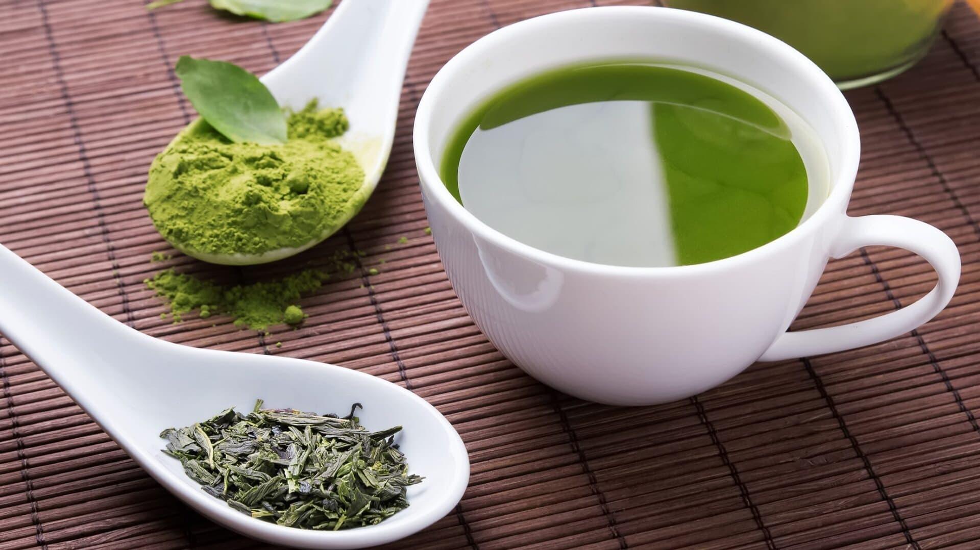 Eine Tasse mit Grünem Tee, daneben zwei Löffel mit Grünteepulver- und Blättern.