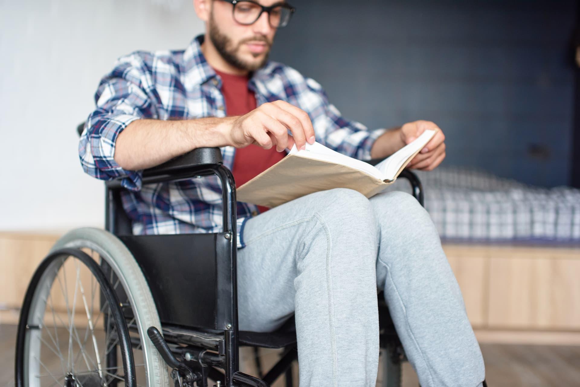 Junger Mann lernt sitzend im Rollstuhl