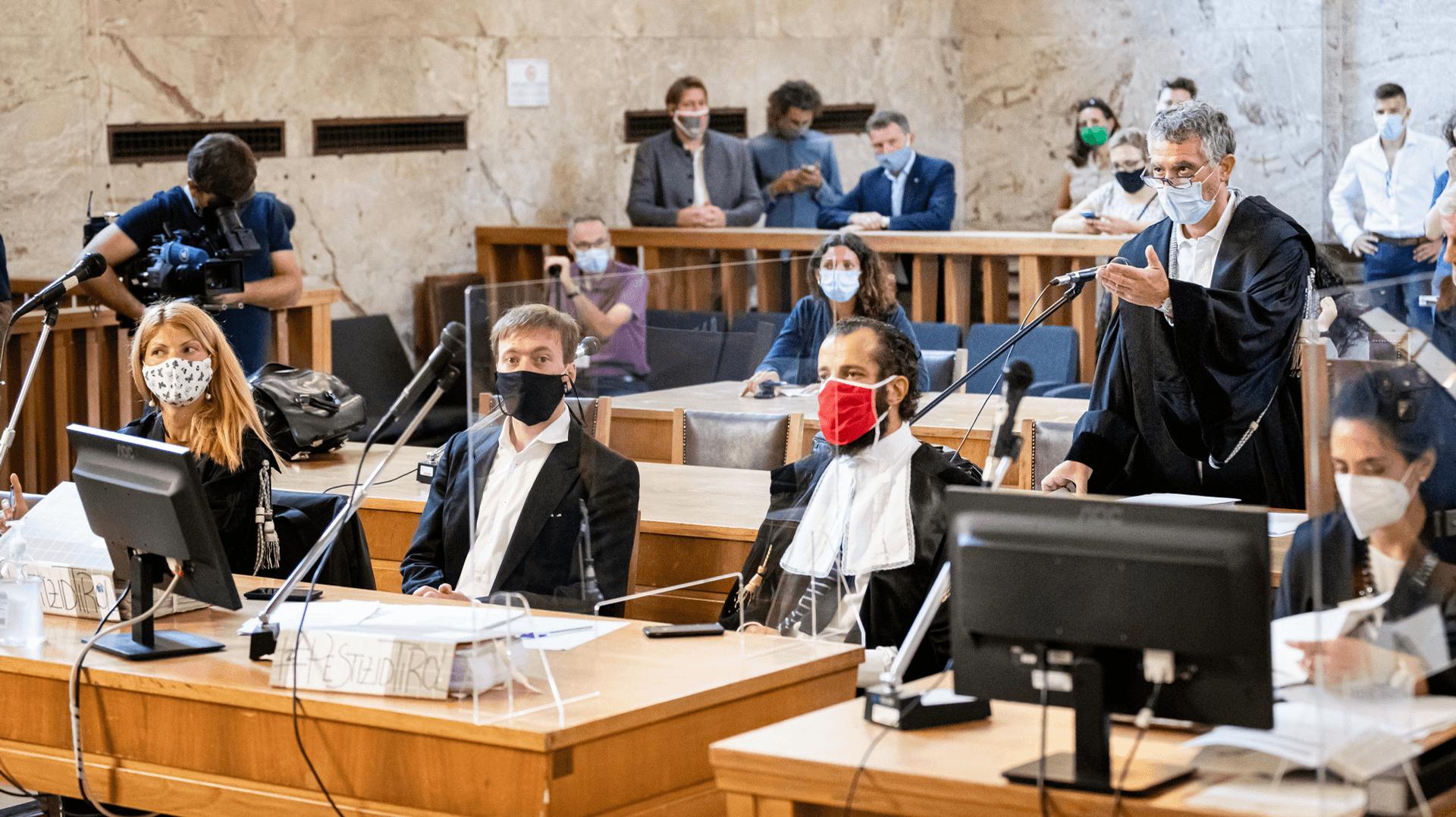 Mehrere Personen mit Atemschutzmasken in einem Gerichtssaal.