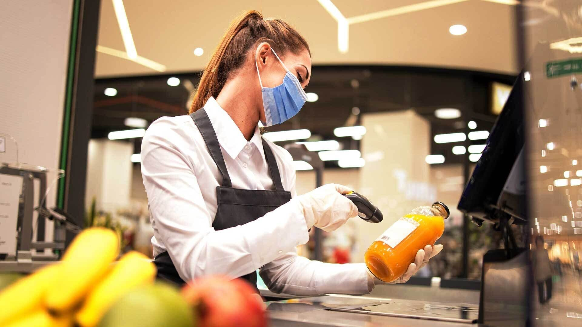 Eine Verkäuferin scannt eine Flasche Saft