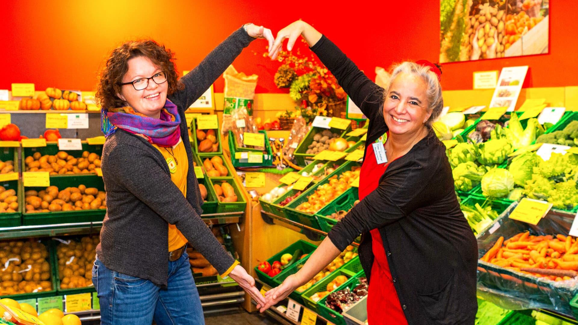 Sabine Vorwald (li.) und Tina Schäfer formen mit ihren Armen ein Herz in der Luft.