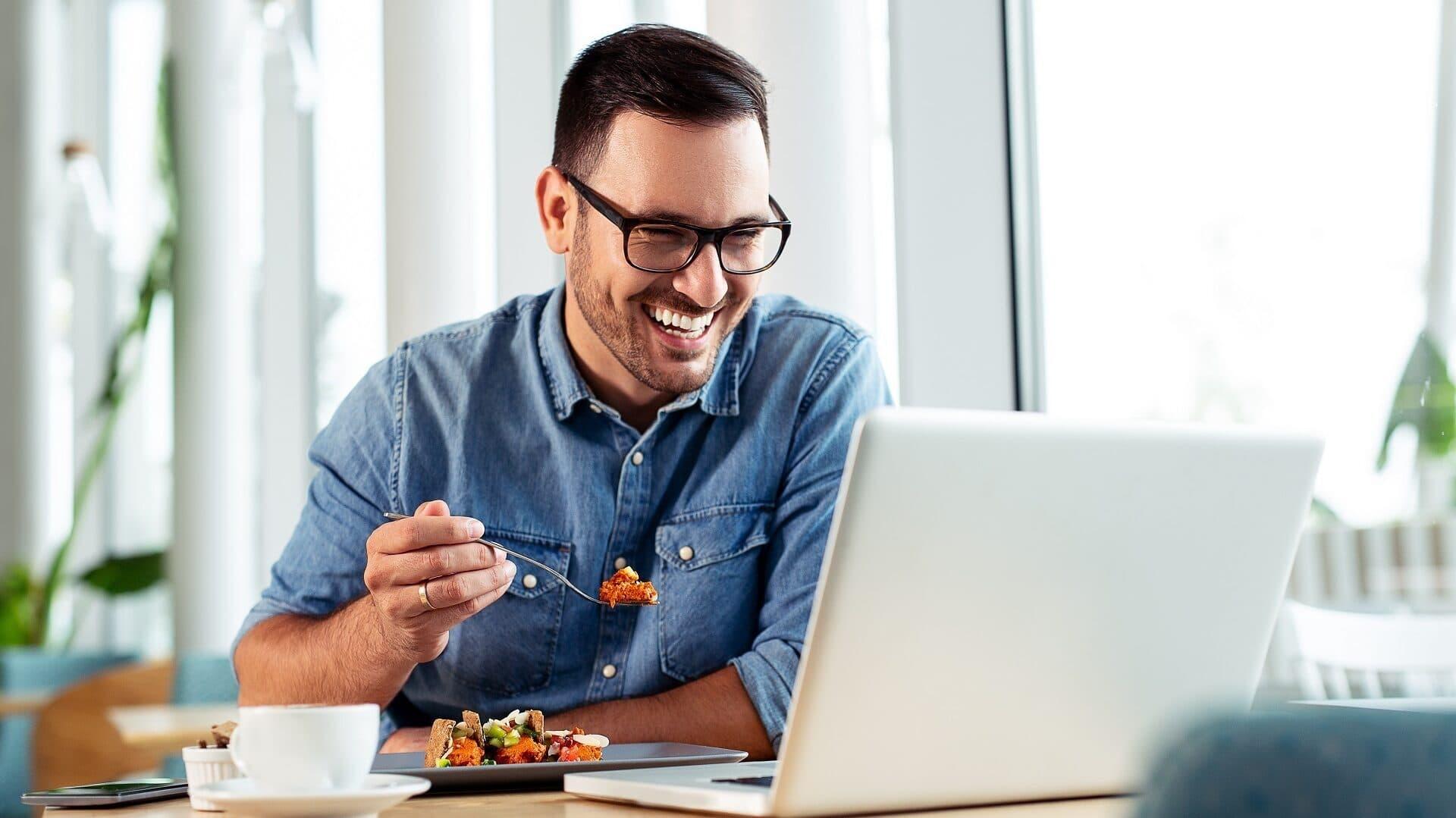 Ein Mann isst und lacht vor seinem Computer