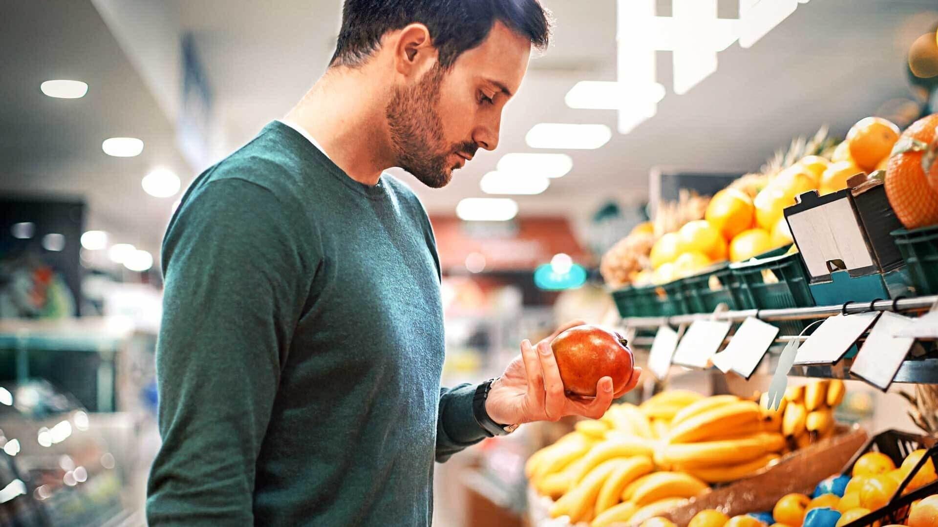 Ein Mann begutachtet einen Granatapfel vor dem Obstregal