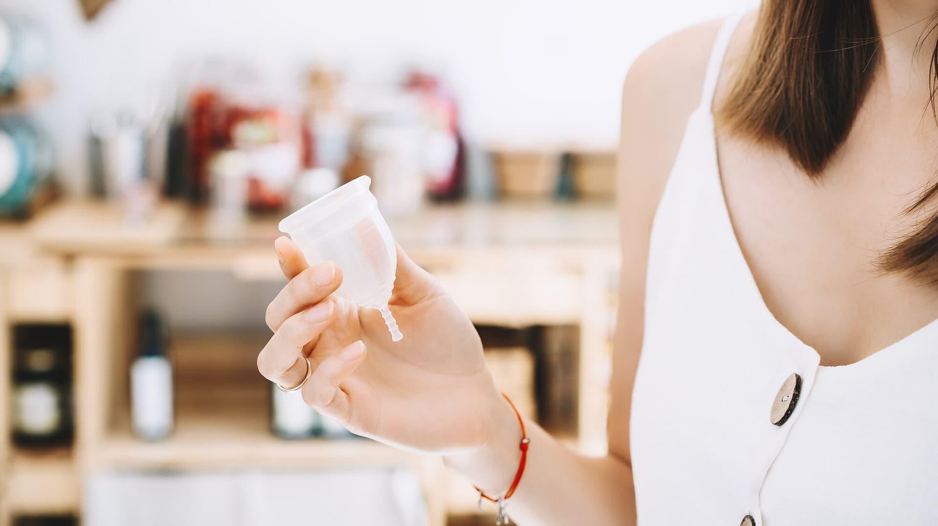 Eine Frau hält eine Menstruationstasse in der Hand