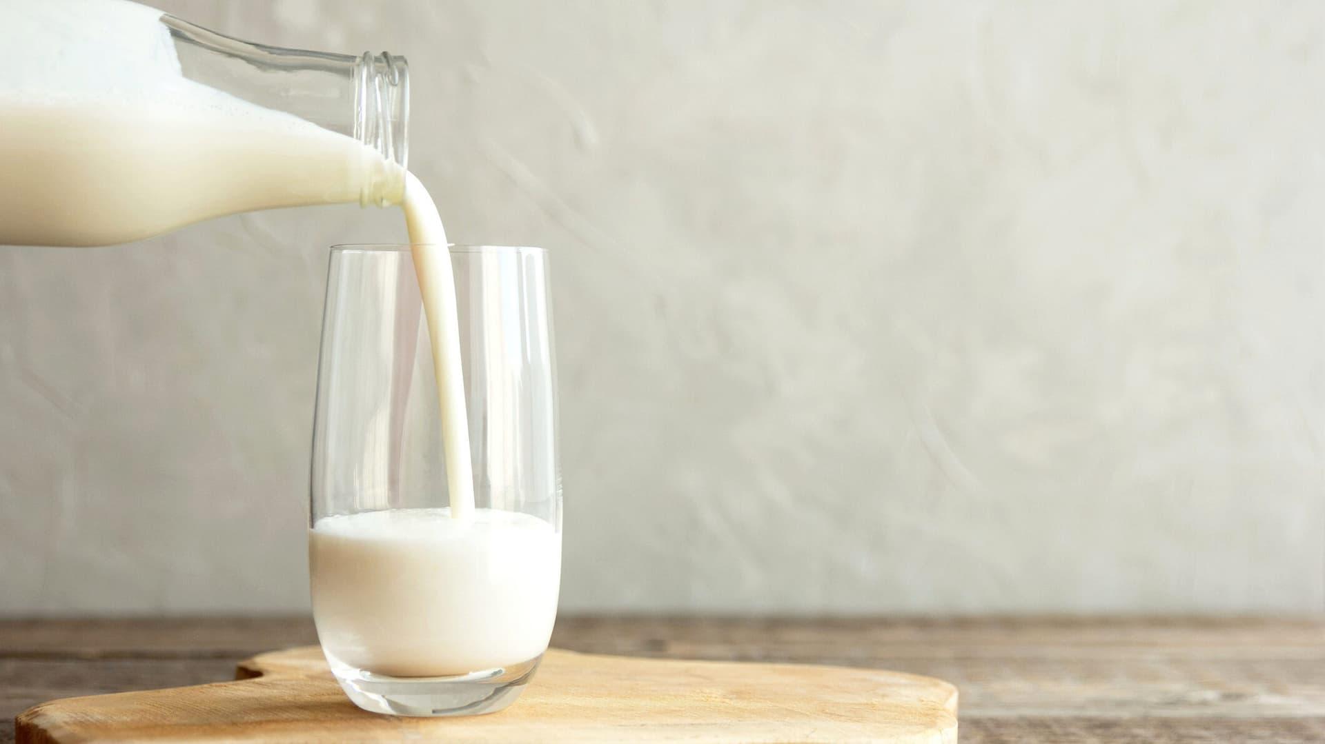 Milch wird in ein Glas gegossen.
