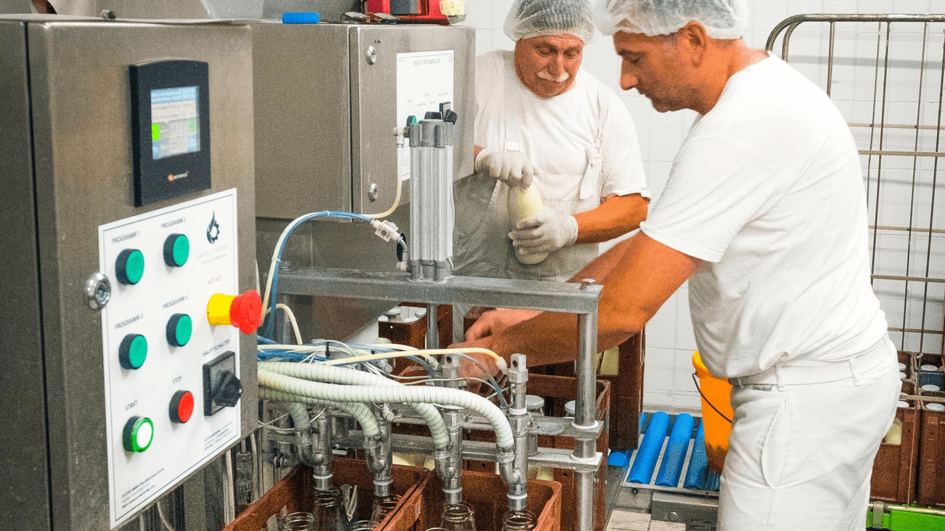 Zwei Personen mit Arbeitskleidung in der Milchverarbeitung