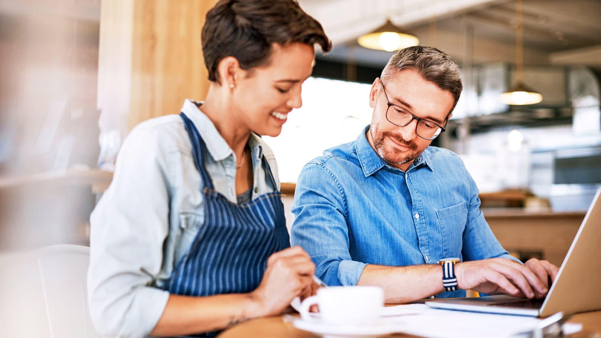 Zwei Personen sitzen bei Kaffee gemeinsam am Computer