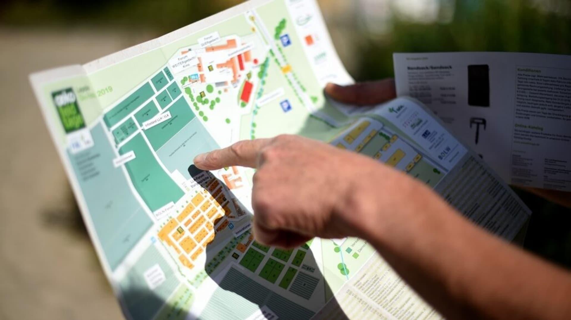 Hand zeigt auf eine Geländekarte