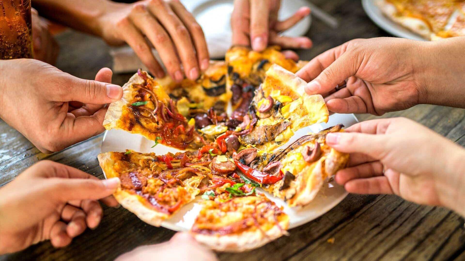 Viele Hände greifen nach einer geschnittenen Pizza