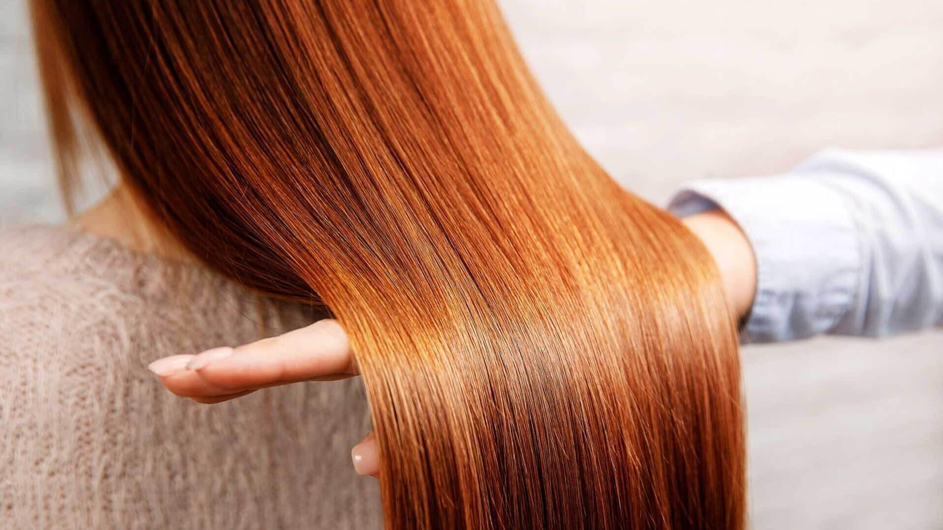 Eine Hand fährt durch langes rotes Haar