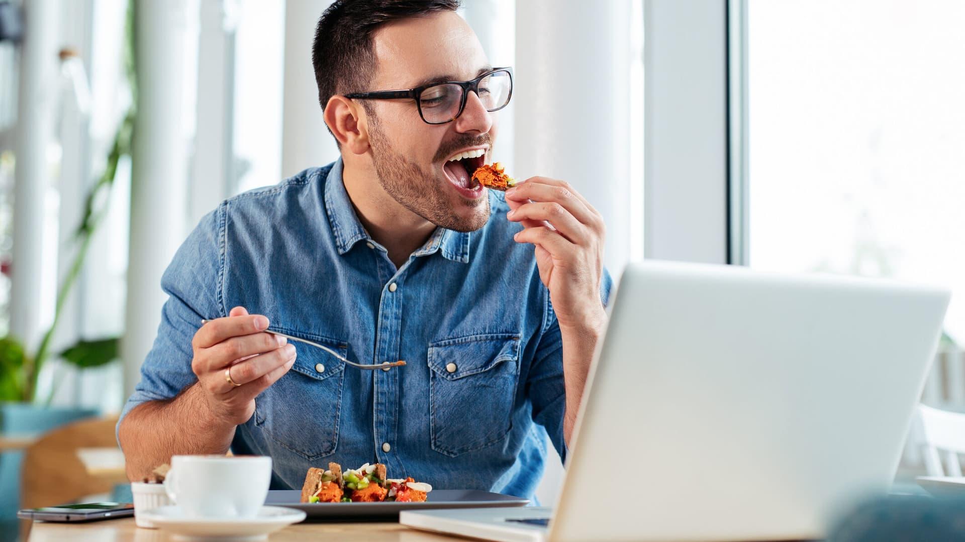 Mann isst vor einem Computer