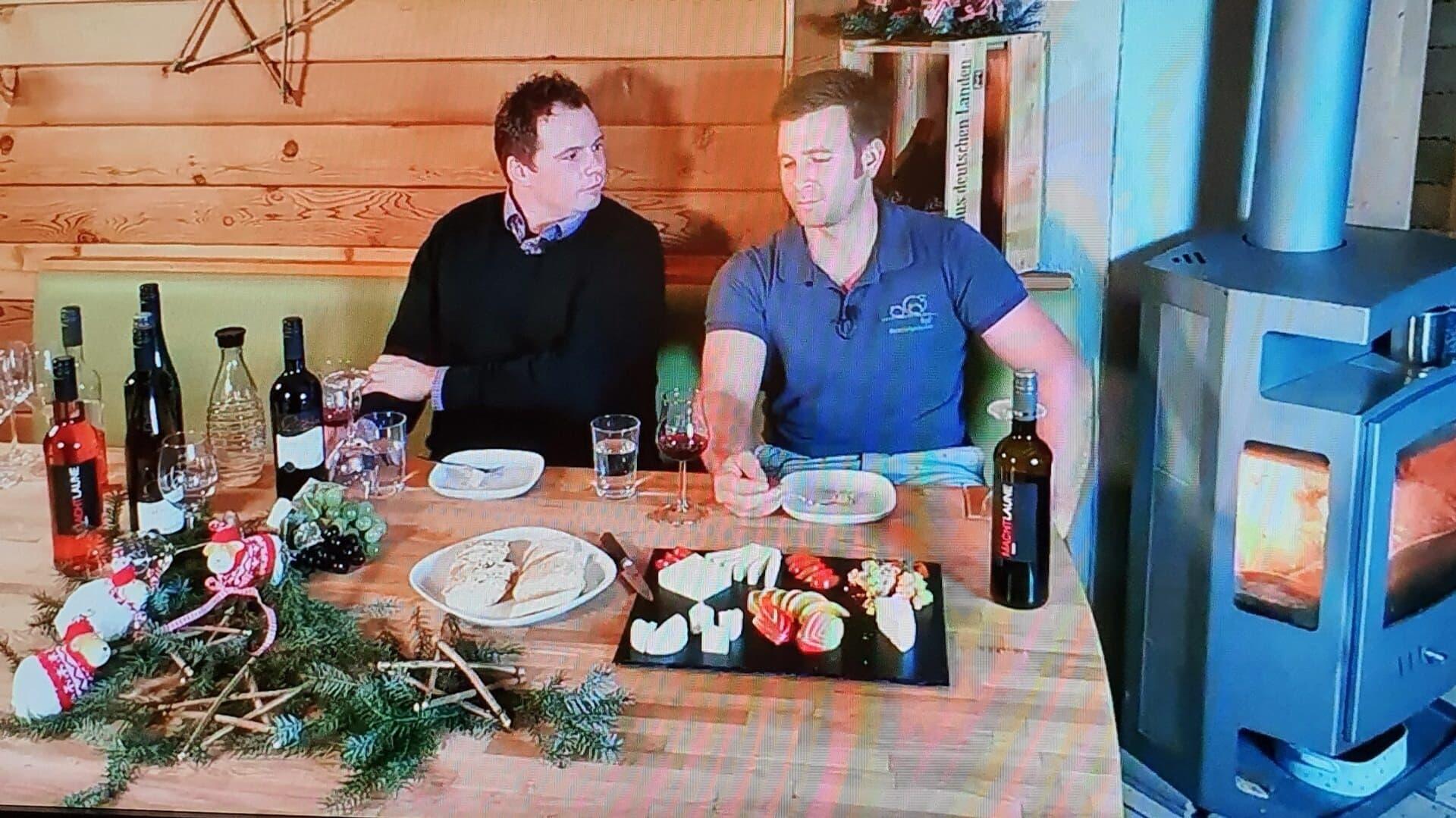 Zwei Männer neben einem Ofen bei einer digitalen Verkostung.