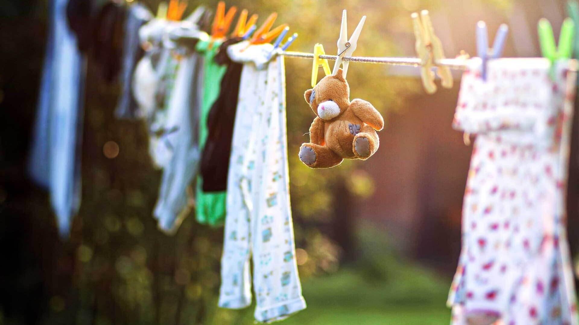 Wäscheleine mit Kinderkleidung und einem Teddy