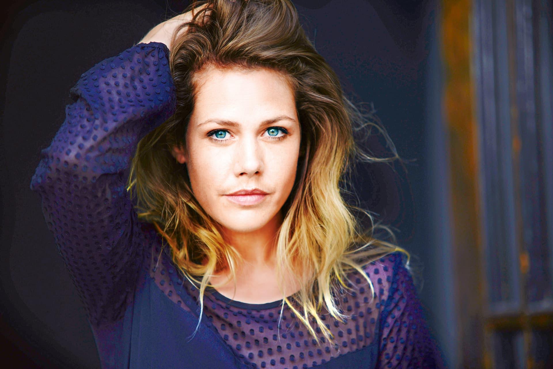 Die Schauspielerin Felicitas Woll blickt, mit der rechten Hand in ihren Haaren, in die Kamera.