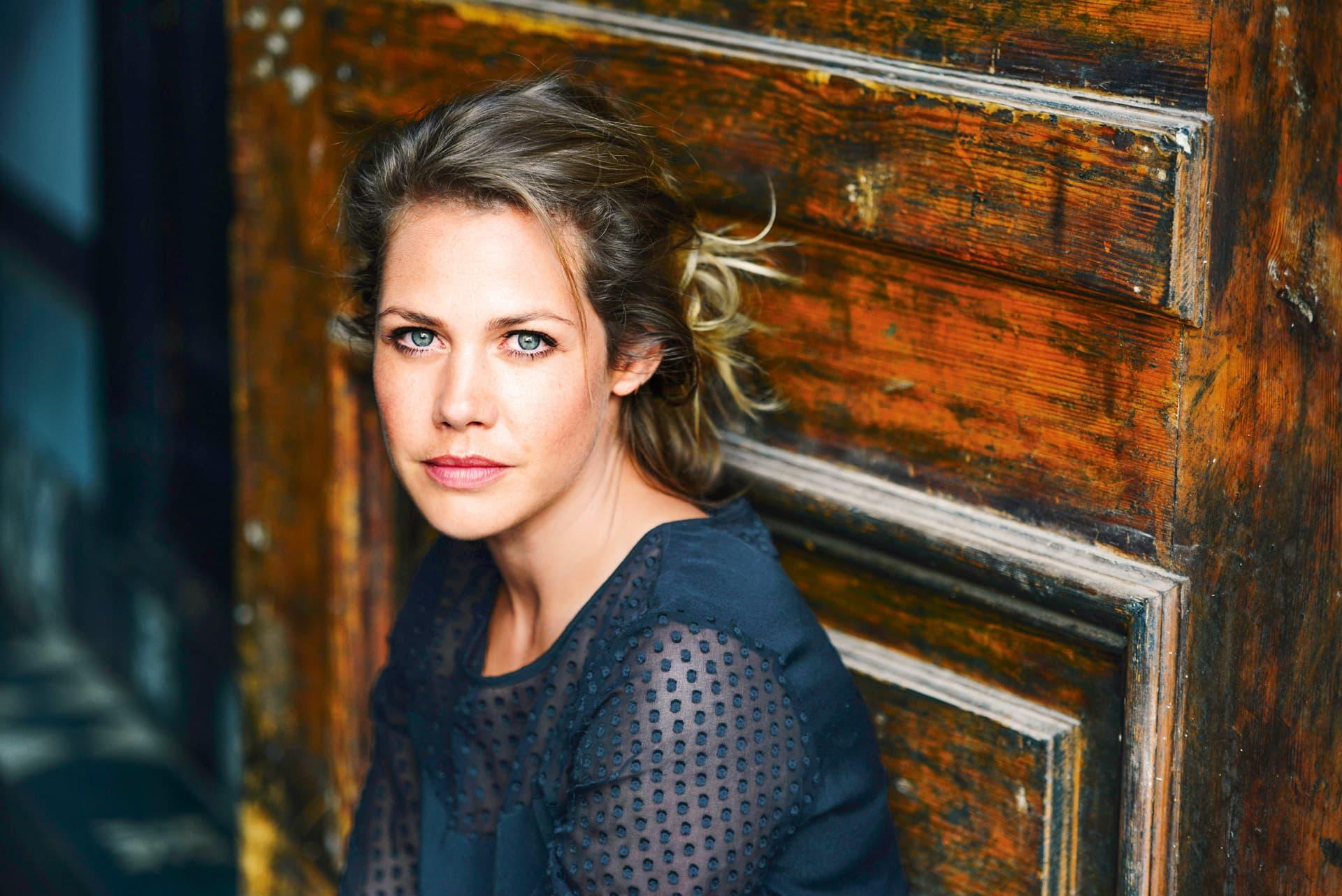 Die Schauspielerin Felicitas Woll blickt, vor einer alten Holztür sitzend, in die Kamera.