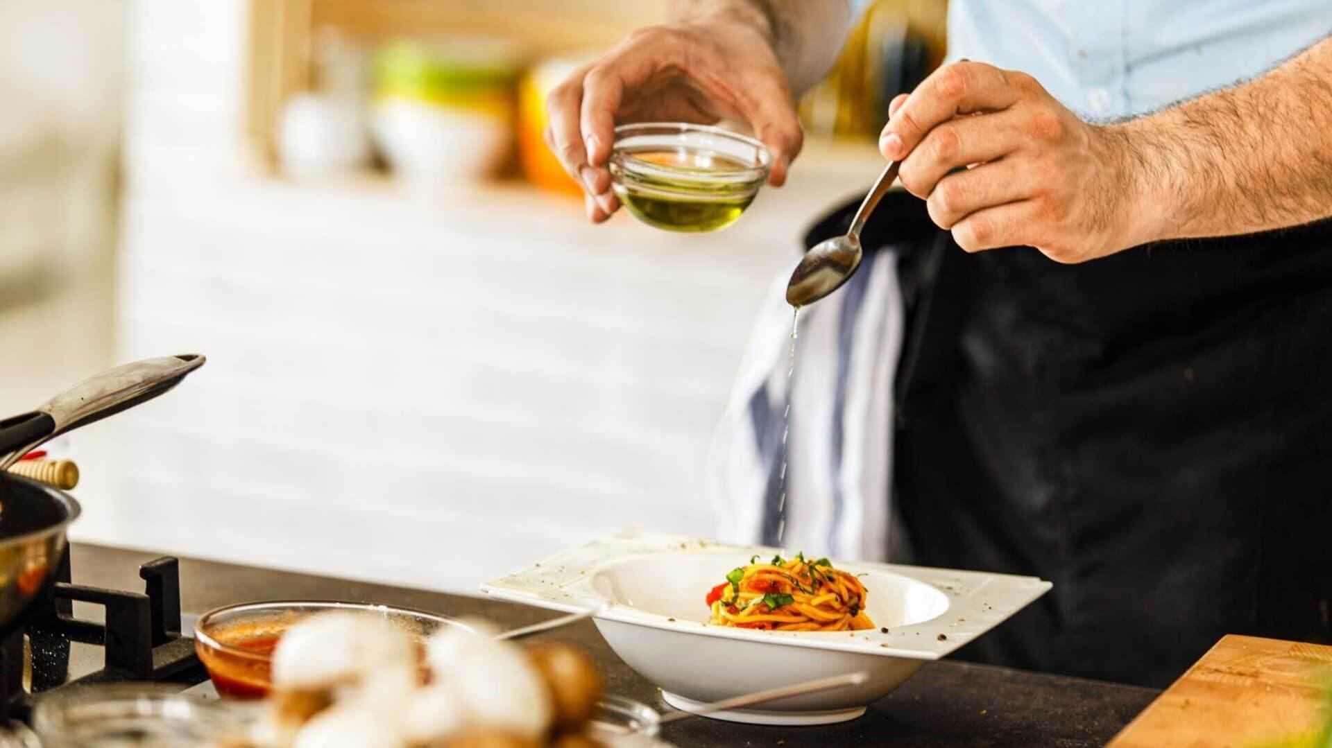 Eine Person würzt Essen mit Würzöl.