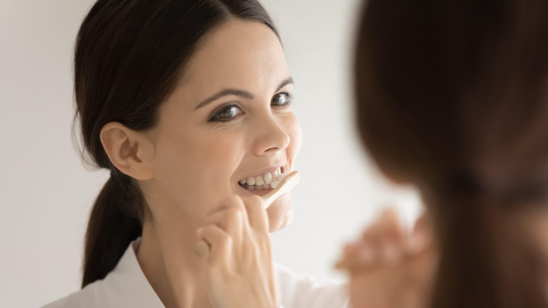 Eine Frau putzt sich die Zähne und schaut dabei in den Spiegel.