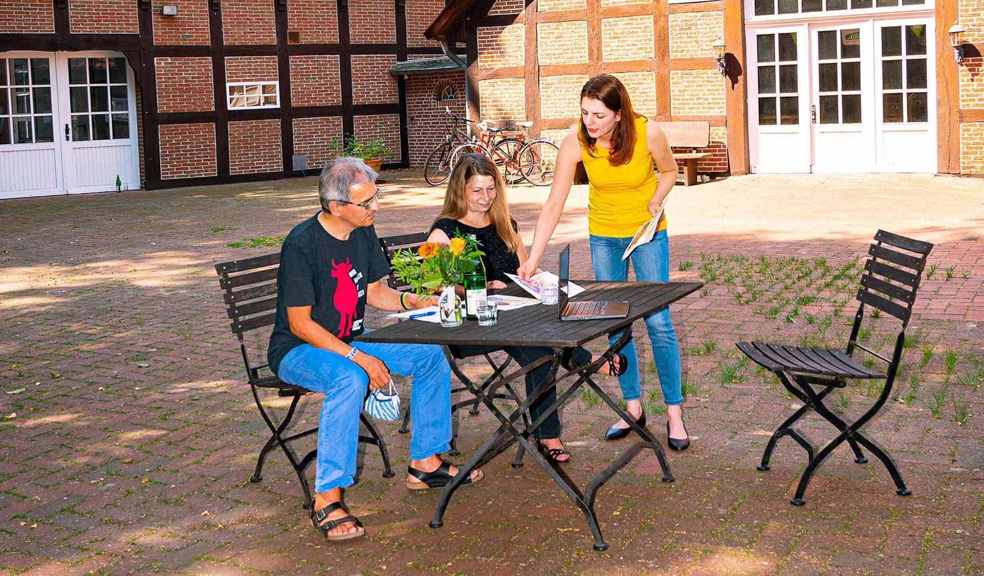 Drei Leute sitzen um einen Tisch und besprechen das Müsli-Design.